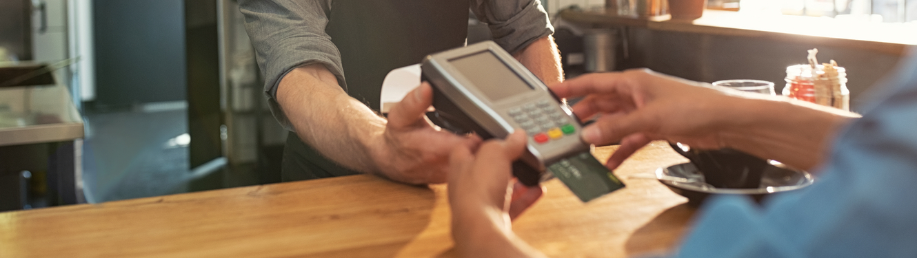 Customer paying a business by credit or debit card using a card machine